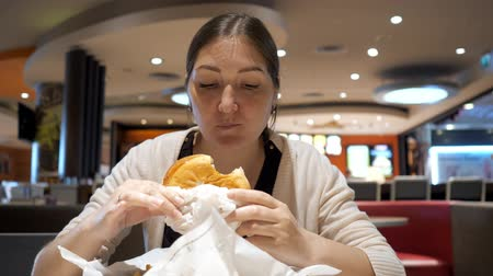 чизбургер : Junk food concept. Young brunette woman is eating burger in fast food restaurant in food court. Hungry girl is biting and chewing her hamburger.