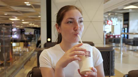 Baku, Azerbaijan, 23-05-2019: Young brunette woman is drinking her beverage milkshake in McDonalds. She is sitting in airport in food court zone. Editorial video.