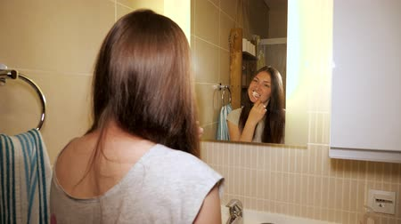 escova de dentes : Young woman is brushing her teeth. She is making daily routine at home bathroom in the morning. Girl is using toothbrush for clean dental oral care. Portrait shot in mirror reflection.