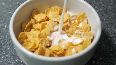 flocos de milho : Preparing fast breakfast with cereal. Pouring milk in bowl with dry cornflakes. Traditional morning food. Stock Footage