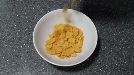 flocos de milho : Dry cereal in morning. Pouring cornflakes in white bowl on grey table preparing breakfast. Traditional meal.