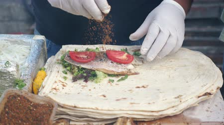 pita : Traditional mediterranean cuisine. Man is making ekmek with fish, greens, tomatoes and seasonings at street market, hands in gloves closeup. Cook wraps the stuffing in pita.