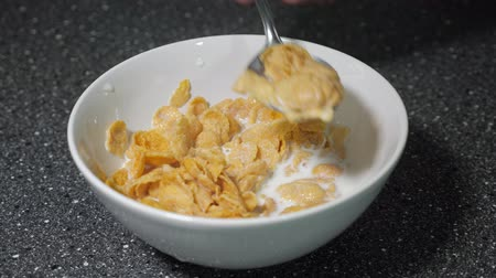 flocos de milho : Preparing fast breakfast with cereal. Man is mixing dry cornflakes and milk in bowl with spoon. He is eating cereal for breakfast. Bachelor usual breakfast.