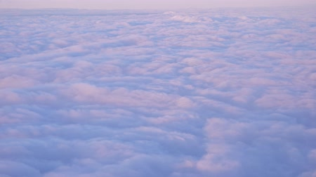 puffy cloud : Beautiful clouds surface in sunset sky, view from plane during flight. Pink and blue cloudscape look like a snow.