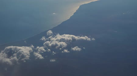puffy cloud : Aerial view from the airplane. Flying over the layer of clouds and looking on landscape through the clouds. Soft sunlight in sky.