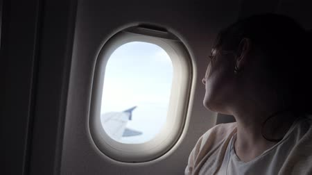 aircraft cabin : Long flight on aircraft. Portrait of sleepy tired woman is looking at plane window. Brunette gierl feeling unwell during the flight.