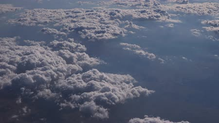 soft earth : Aerial view from the airplane. Flying over the layer of clouds and looking on landscape through the clouds. Soft sunlight in sky.