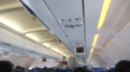 attendant : Flight attendant young woman distributes food and drinks on the board of airplane. Passengers sit in their seats and watch TV, blurred Stock Footage