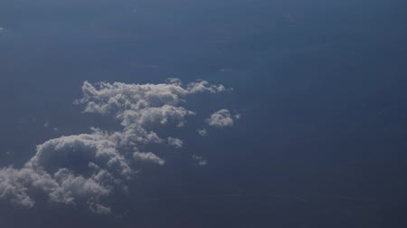sztratoszféra : Aerial view from the airplane. Flying over the layer of clouds and looking on landscape through the clouds. Soft sunlight in sky.
