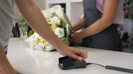 nyugta : Woman seller florist gives a huge beautiful bunch of flowers to customer. Man buys bouquet in flower shop paying by card in payment terminal, hands closeup. Work day in floristry studio.