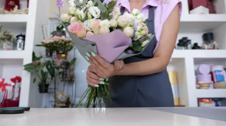 virágárus : Wrapping of the bouquet in the floristry studio. Florist is packaging bouquet from pink and white roses, blue gypsophila and leaves in paper on the table in flower shop, closeup hands.