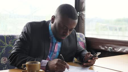 dark skinned : Black guy is making paperwork. Afro american businessman is filling documets in summer tent cafe looking in smartphone. Writing papers. Hot cup of coffee on the table. He wears shirt and suit jacket.