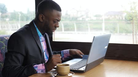dark skinned : Afro american man has breakfast. Black businessman works on laptop with smartphone in cafe and drinks coffee. He types on computer looking at mobile phone screen. Wears in shirt and suit jacket.