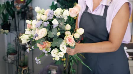 gypsophila : Professional florist woman creates lovely flower bouquet with roses, leaves and gypsophila. Blonde middle aged woman in uniform works in flower shop. She makes bunch of tender colours pink and yellow.