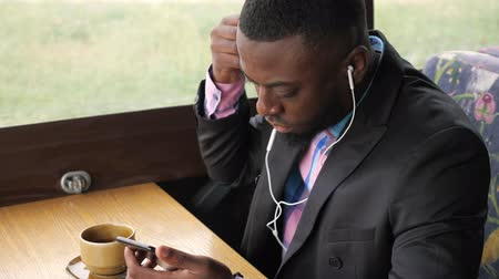 dark skinned : Black businessman listens music on smartphone in earphones sits in cafe and drinks coffee. He is putting on earpieces in his ears and including music. Afro american guy wears suit jacket and shirt. Stock Footage