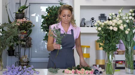 gypsophila : Professional florist at work in flower shop. Woman makes bouquet from pink roses, blue gypsophila and green leaves. She is in uniform standing near the table.