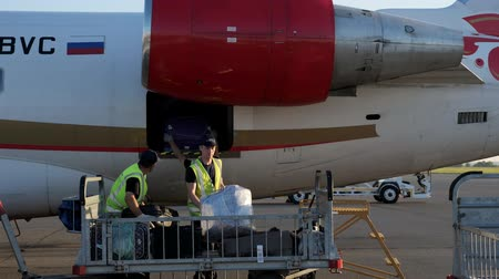 Nizhnekamsk, Russia, 25-05-2019: Porters load luggage in plane before departure. Ground staff prepare aircraft to flight in Begishevo airport. Workers put suitcases in luggage compartment of jet.