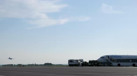 Nizhnekamsk, Russia, 25-05-2019: Airfield with planes on runway, bus and people. Aircfart takes off on background. Passengers come out of plane Pobeda airlines on stairs and get on bus. Spotting.