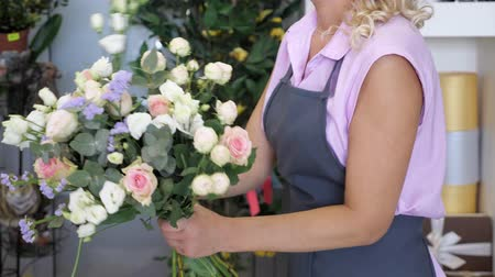 dekoratör : Professional florist woman creates lovely flower bouquet with roses, leaves and gypsophila. Blonde middle aged woman in uniform works in flower shop. She makes bunch of tender colours pink and yellow.