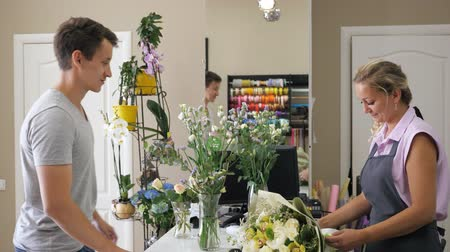 sorriso largo : Young man customer buys huge beautiful bunch in flower store. Woman florist sellor gives flower bouquet to man customer in modern floristry shop. Work day in floral business.