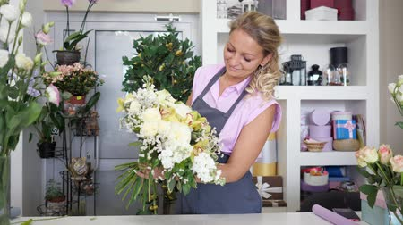 dekoratör : Working in flower shop. Professional florist is creating huge beautiful bouquet from fresh white roses, yellow lilys and green leaves. Seller on her workplace in uniform holding flower bunch.