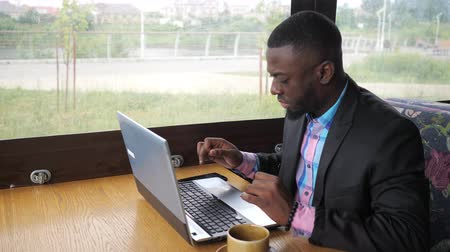 hírnök : Afro american businessman is typing a message on laptop sitting in summer cafe near window. Black man writes on computer, texting e-mail. Working with cup of coffee, close-up