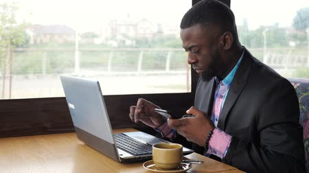 メッセンジャー : Afro american man has breakfast. Black businessman works on laptop with smartphone in cafe and drinks coffee. He types on computer looking at mobile phone screen. Wears in shirt and suit jacket.