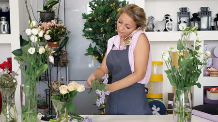 decorador : Professional woman florist talks on smartphone taking order and makes bouquet working in flower shop. Mature woman in apron in floristry studio creating beautiful bunch. Self-employed people concept.