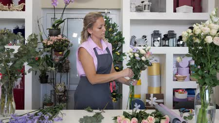 decorador : Professional florist at work in flower shop. Woman in uniform standing near the table and makes bouquet
