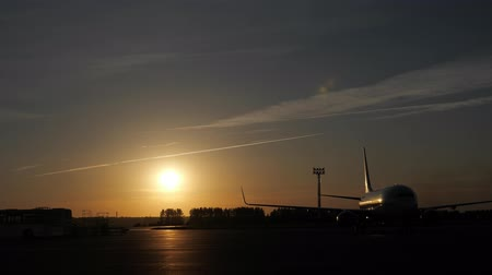 tankowanie : Airport working on airstrip. Ground staff people on runway with planes. Planes on runway at sunset in airfield take off and prepare to flight. Big yellow sun in dark sky. Aircraft silhouettes in dark. Wideo