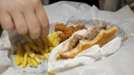 food court : Junk food concept. Hungry girl has a lunch in fast food restaurant. Woman is eating french fries in fast food restaurant with chicken and burger in white paper, food closeup.