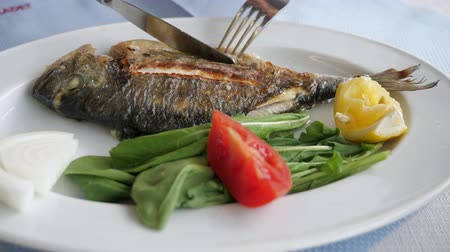 villa : Full frying small fish served with piece of lemon, tomato and arugula salad leaves in white plate. Man is eating fish with fork and knife in restaurant, dish closeup.