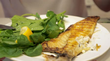 segurelha : Full frying small fish served with piece of lemon and arugula salad leaves in white plate. Woman is eating fish with fork and knife in restaurant, close-up. Stock Footage