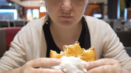 food court : Junk food concept. Unrecognizable young woman is eating french fries and hamburger in fast food restaurant. She is holding burger in one hand and taking potato other hand, mouth closeup. Stock Footage