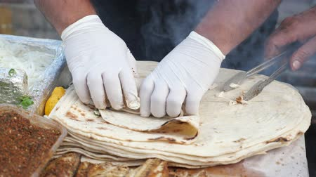 stuffing : Traditional mediterranean cuisine. Man is making ekmek with fish, greens, tomatoes and seasonings at street market, hands in gloves closeup. Cook wraps the stuffing in pita.