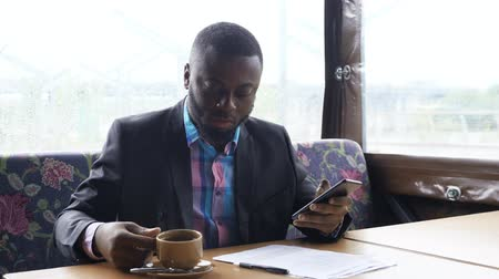 hírnök : Afro american businessman is browsing smartphone sitting in cafe. He is typing a message chatting in messenger and drinking a cup of coffee