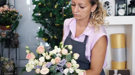 decorador : Professional florist woman creates lovely flower bouquet with roses, leaves and gypsophila. Blonde middle aged woman in uniform works in flower shop. She makes bunch of tender colours pink and yellow.