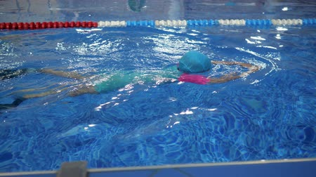 flippers : Child girl in goggles, swimsuit, cap and flippers is training swimming in pool. She swims in professional pool with transparent blue water in slow motion. Workout for little swimmer.