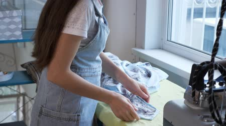 varrónő : Clothing manufacture. Seamstress ironing details of clothes in sewing workshop of tailoring business. Professional tailor at work. Dressmaker working in professional sewing atelier. Stock mozgókép