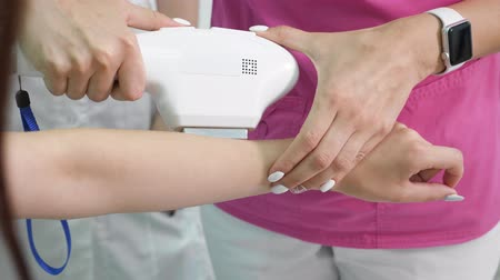 depilation laser : experienced therapist makes laser epilation on lady hand in modern beauty salon with special equipment closeup