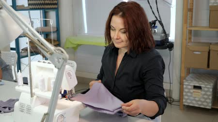 шитье дамского платья : Dressmaker sewing clothes. Fashion designer sewing new model of clothes. Seamstress woman works on sewing machine in tailoring workshop business. She stitches details for future clothing.
