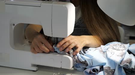 самодельный : Processing tissue of fabric edge. Seamstress working at sewing machine making stitches seams with straight stitch on purple cloth, hands closeup. Clothing tailoring business manufacture. Стоковые видеозаписи
