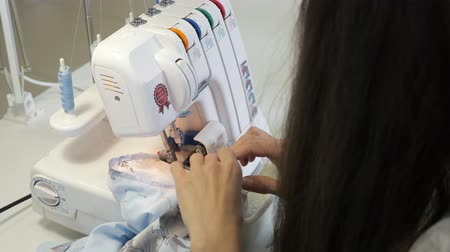 самодельный : Finish detail with serger overlock stitch. Seamstress brunette woman sewing in workshop atelier on overlock cloth edges, hands closeup. Processing tissue overlock. Tailoring business in factory.