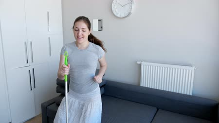 mopping : Happy young woman is cleaning her home. She is washing floor using mop, singing a song and dancing in her modern flat. Playing on mop as on guitar.