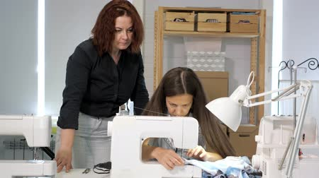 varrónő : Dressmaker teaches new employee to work in workshop. Cutting and sewing courses. Seamstress teacher controls looks how student sew on sewing machine in workshop. Traineeship concept. Probation period.