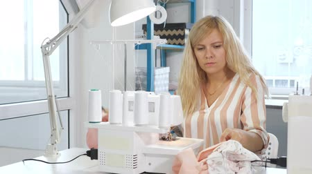 самодельный : Processing tissue overlock. Seamstress working at sewing workshop sews on overlock cloth edges. Clothing manufacture. Stitches seams with straight stitch and finish them with serger overlock stitch.