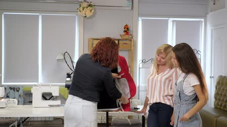 шитье дамского платья : Cutting and sewing courses. Dressmaker shows women ways of sewing pockets on clothes on a mannequin. Seamster teaches her students to sew clothes show details on jacket on courses. Tailoring business. Стоковые видеозаписи