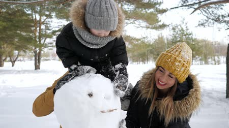 сугроб : Happy family, mom, son and dad are making a snowman in winter park. Son is sitting on dads neck Стоковые видеозаписи