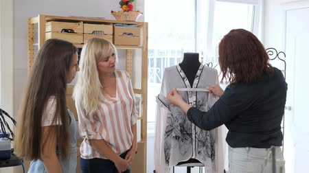 magyarázza : Cutting and sewing courses. Dressmaker explains to two women how to take measurements for tailoring in workshop. She measures the mannequin using tape measure. Business tailoring handmade clothes. Stock mozgókép