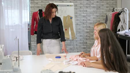 самодельный : Cutting and sewing courses. Seamstress teacher talks to students two woman about ways of processing tissue in workshop. Handmade tailoring and cutting clothes, needlewoman hobby. Sewing training.